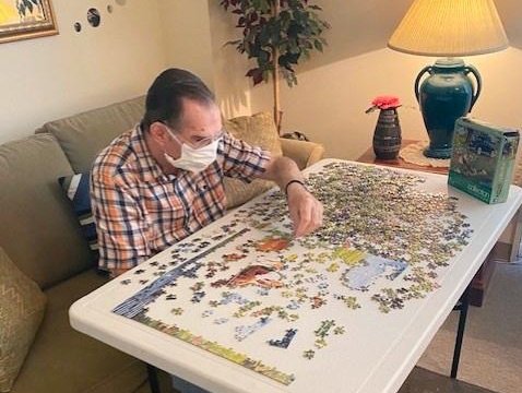 older man in a mask sitting at a table and doing a jigsaw puzzle