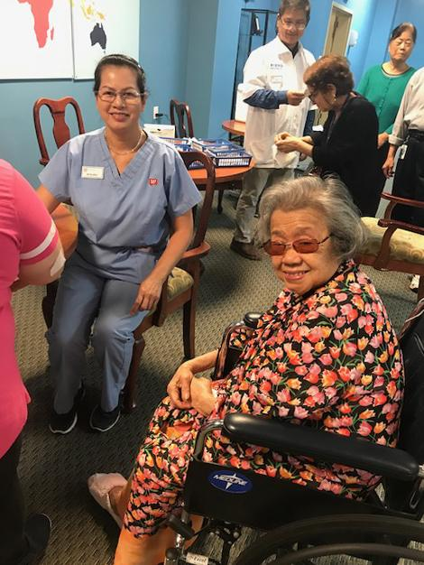 Woman in wheelchair with a nurse in background