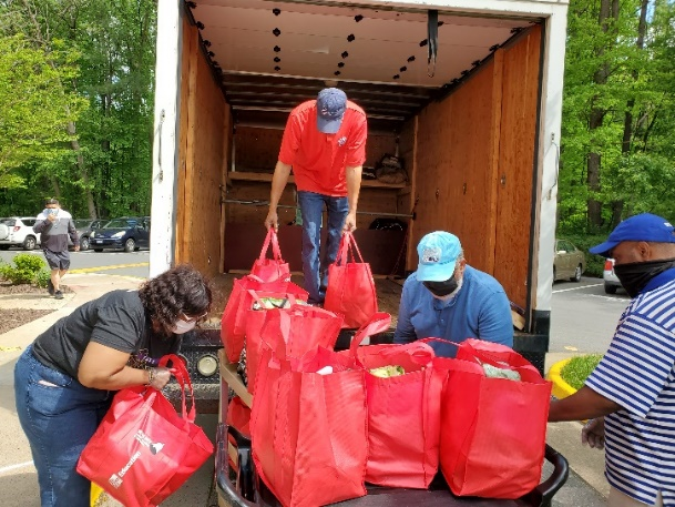 3 people unloading red bags of groceries from a truck