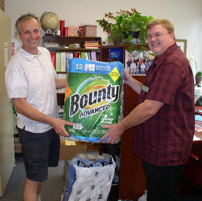 two men holding a large package of paper towel rolls
