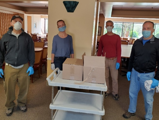 4 masked volunteers with a cart of boxes