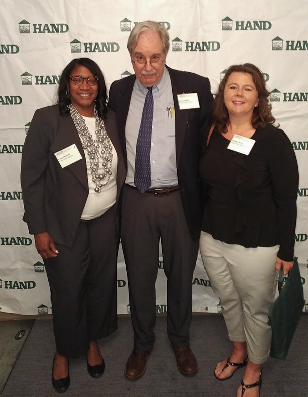 Three people standing in front of a background of HAND logos