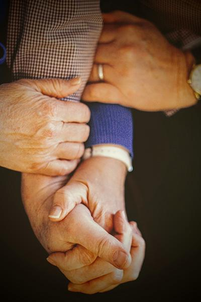 closeup view of 2 hands clasped with 2 hands holding arms