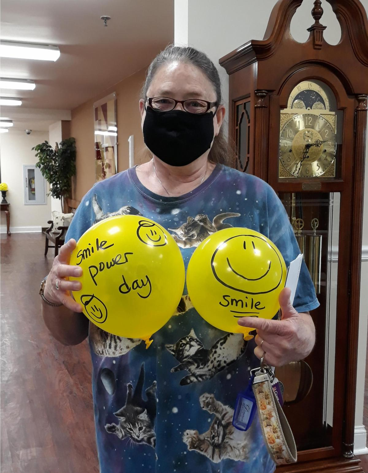 woman in mask holding 2 yellow balloons that have happy faces on them