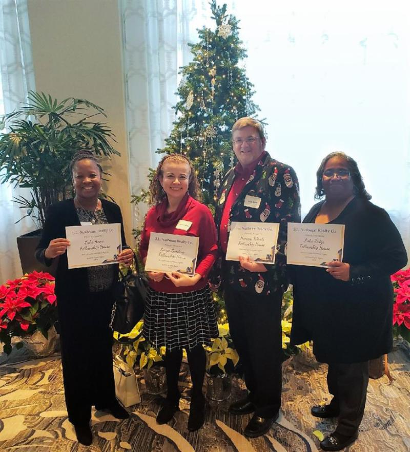 4 people holding certificates in front of a Christmas Tree