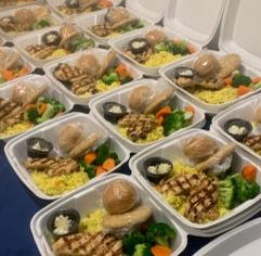 take-out boxes containing chicken and vegetables