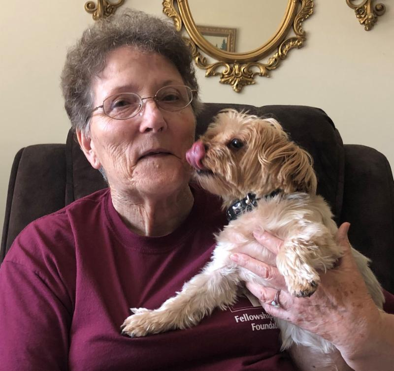 Woman with small dog that is licking her face