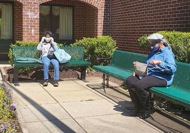 2 people sitting far apart on 2 different benches in a courtyard