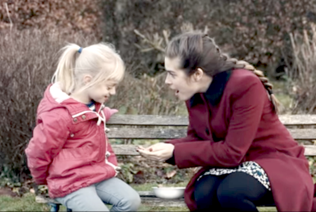 Libby, a deaf girl, is offered treats by her tutor Joanne