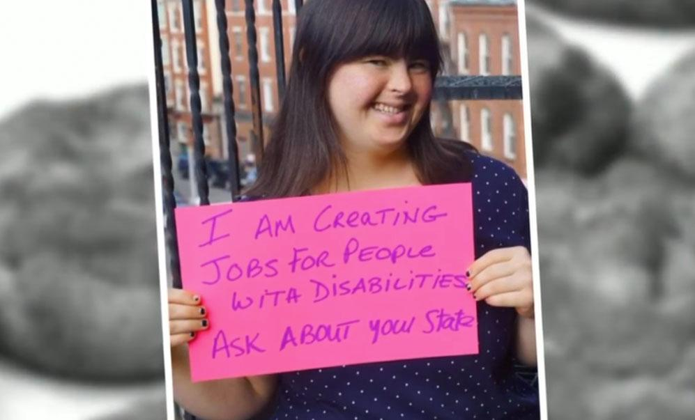 Collette Divitto, entrepeneur with Downs syndrom, holding a bright pink sign about employing people with disabilities