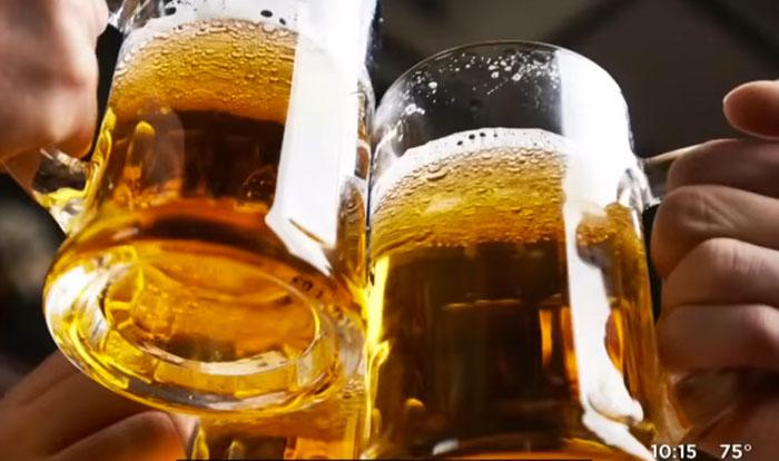 video still from CBS news report, i,age of beer mugs toasting