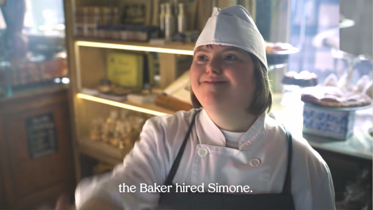 Simone, a young lady with Down Syndrome, smiling as she shakes the hand of the Baker who hired her.