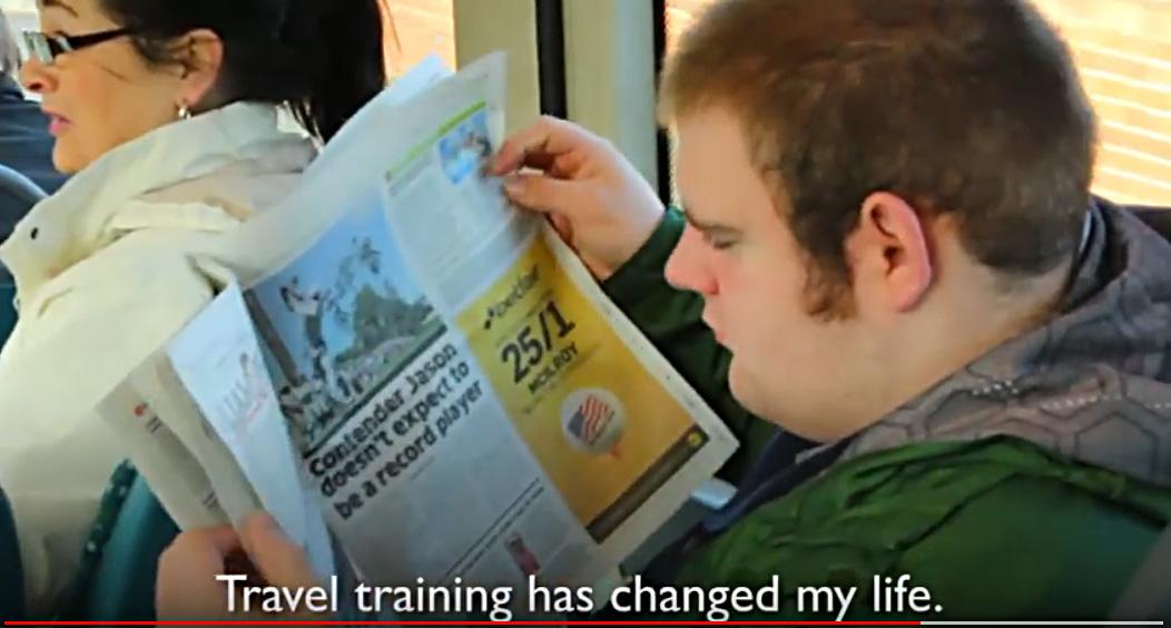 Young man with a disability reading a newspaper while riding on a bus