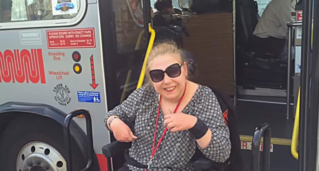 Video still of a young woman in a motrized wheelchair deboarding a city bus
