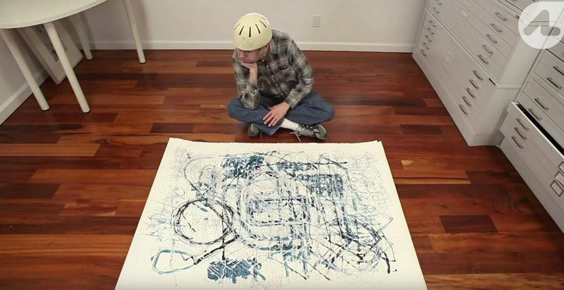 Danny Miller sitting on the floor with his artwork