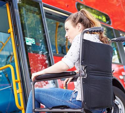 female student in wheelchair boarding a public bus