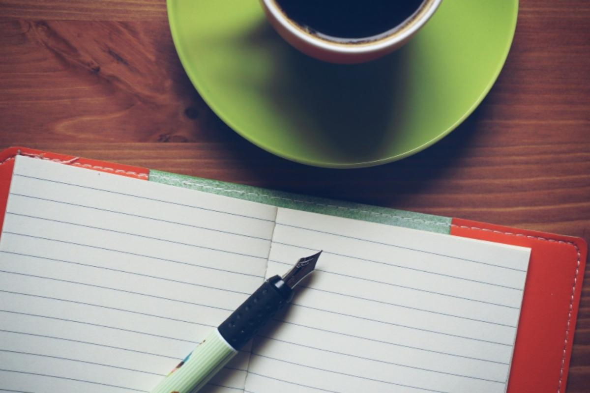 journal, pen, and cup of coffee