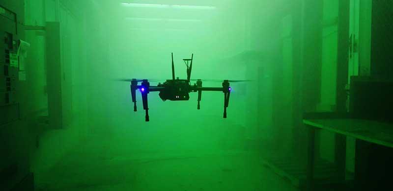 A drone flies through a dark room