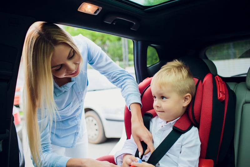family_ transport_ road trip and people concept - happy woman fastening child with safety seat belt in car