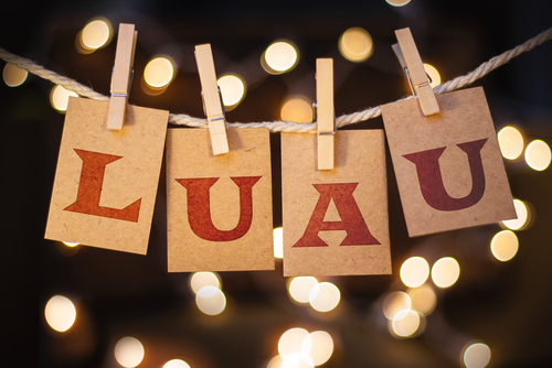 The word LUAU printed on clothespin clipped cards in front of defocused glowing lights.