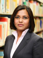 Indian woman in with grey jacket and pink shirt in front of bookcase