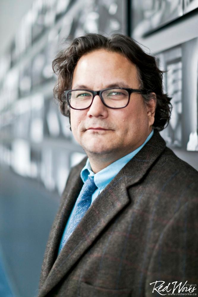 A picture of Jesse. Its a side pose. He is looking at the camera. He is wearing glasses, a brown coat and blue shirt.