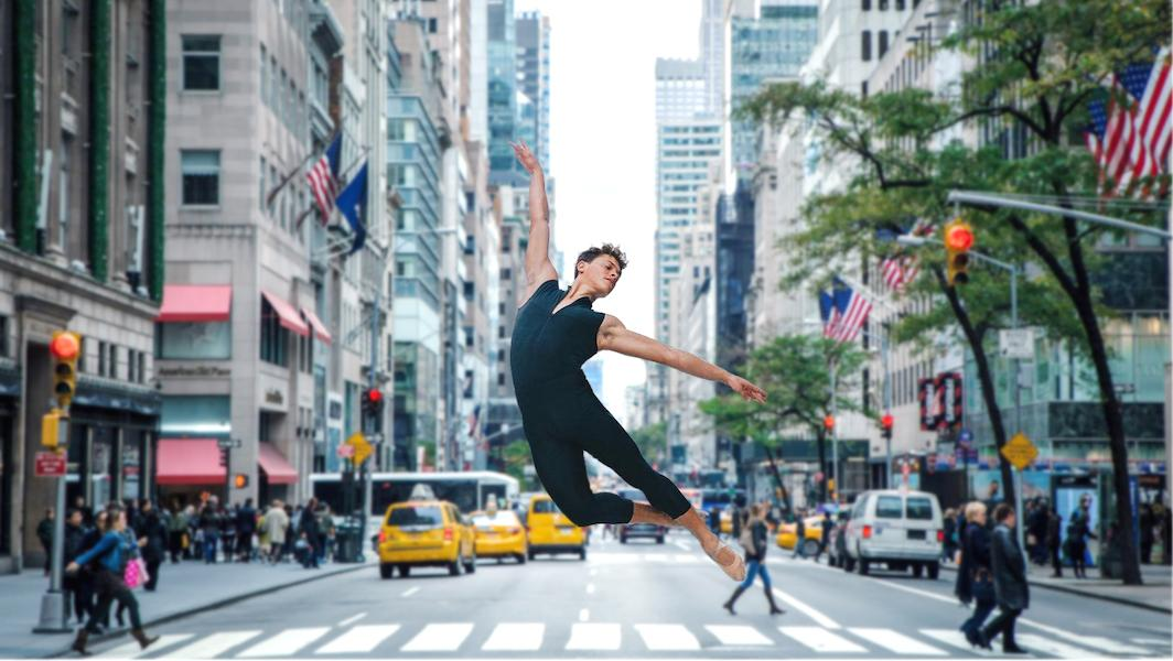 [Image Description: An image from the documentary, CUBAN DANCER, shows a young person wearing a blue unitard and beige ballet shoes jumping elegantly in the middle of a NYC crosswalk. Pedestrians and cabs are out of focus in the background.]