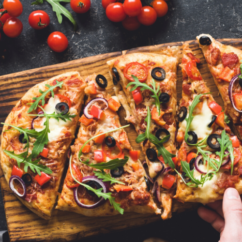 Flatbread pizza with onions_ tomatoes_ arugula and olives