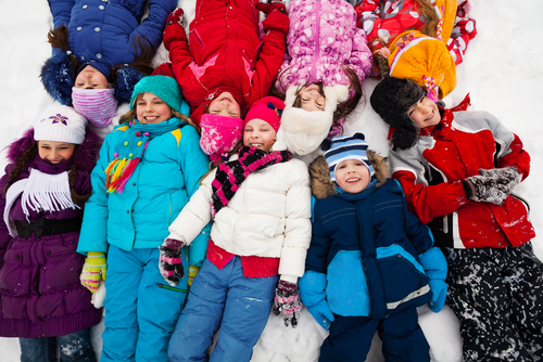 Large group of kids laying in snow together in one big lump_ view from above
