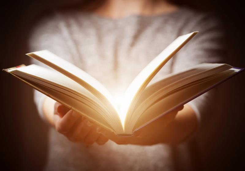 Light coming from book in woman s hands in gesture of giving_ offering. Concept of wisdom_ religion_ reading_ imagination.