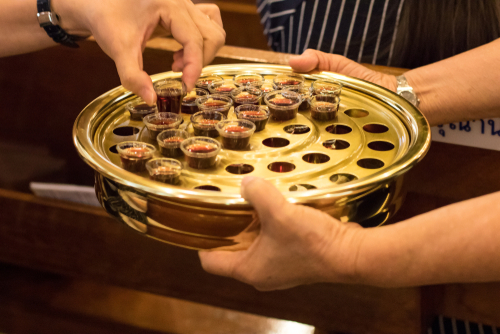 Faithful elder passing a tray contains cups of Holy communion spirit grape wine in the church