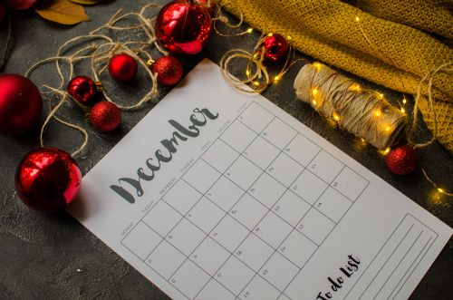 2019 year end review_ date planning_ appointment_ deadline or holiday concept on wooden table next to black clean calendar on month of December.