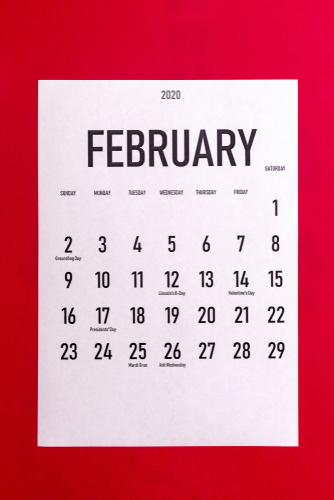 February 2020 calendar with holidays on red paper background