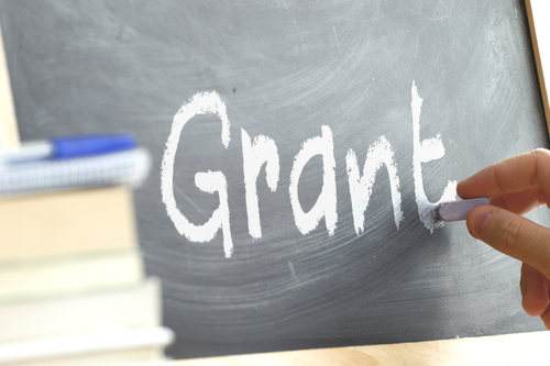 A person writing the word Grant on a blackboard. Some school materials and copy space.
