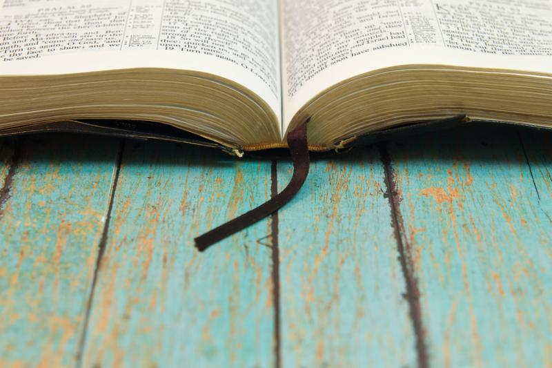 An old open Bible on a rustic wooden plank with room for print