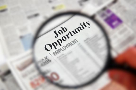 Magnifying glass over a newspaper headline that says Job Opportunity and employment