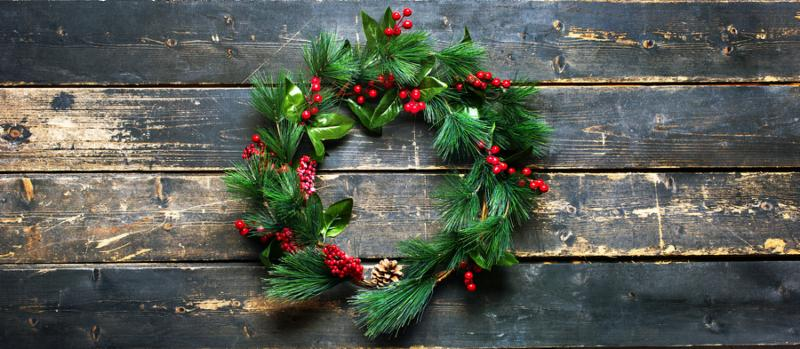 Holiday Banner Green Christmas Decorative Wreath on Dark Planks Wooden Vintage Background top view Happy New Year greeting card Winter xmas theme flat lay. Copy Space for text
