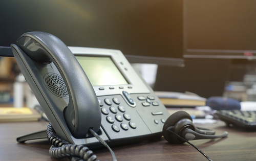 close up soft focus on telephone devices at office desk for customer service support concept