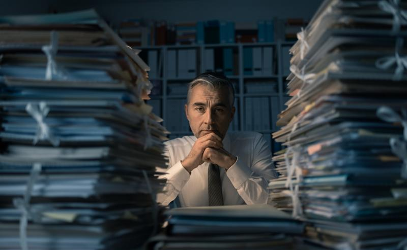 Desperate businessman working in the office late at night and overloaded with work_ his desktop is covered with paperwork  business management and deadlines concept