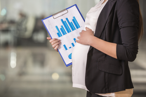 Close-up. Pregnant adult businesswoman working at her working place in office.