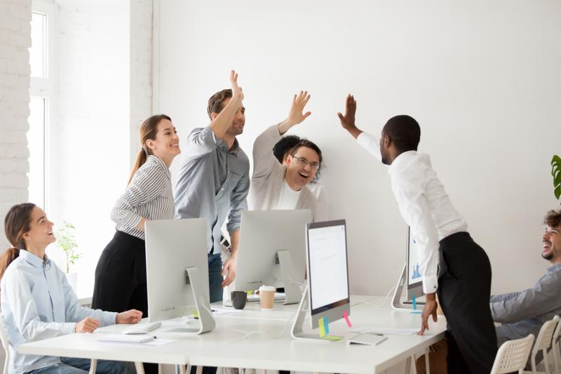 Happy multi-ethnic employees sales team giving high five together celebrating corporate success and good relations_ diverse group of office people joining hands excited by common victory achievement