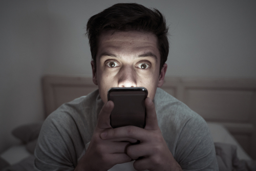 Young mobile phone addict man awake at night in bed using smartphone for chatting_ flirting and sending text message. In communication_ Internet addiction and Social media network abuse concept