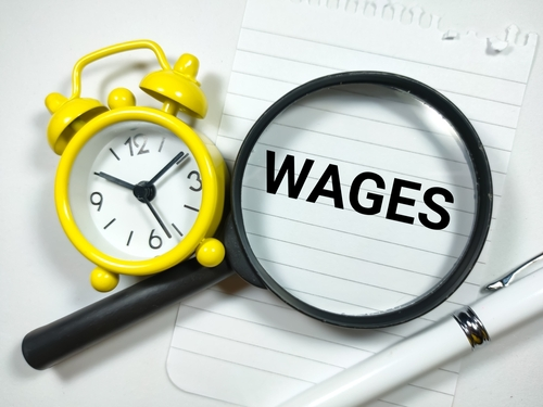 Business concept.Text WAGES writing on notepaper with clock_pen and magnifying glass on white background.
