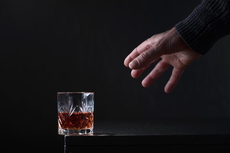 Man s hand reaches for a glass of alcohol. Conceptual image on the subject of alcoholism. Copy space for your text.