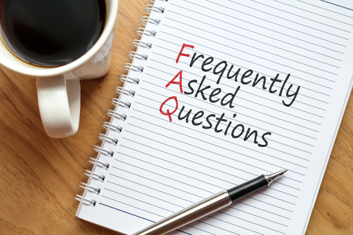 Notebook_ pen and a cup of coffee on wooden table. Notebook written FAQ - Frequency Asked Question_ business concept.