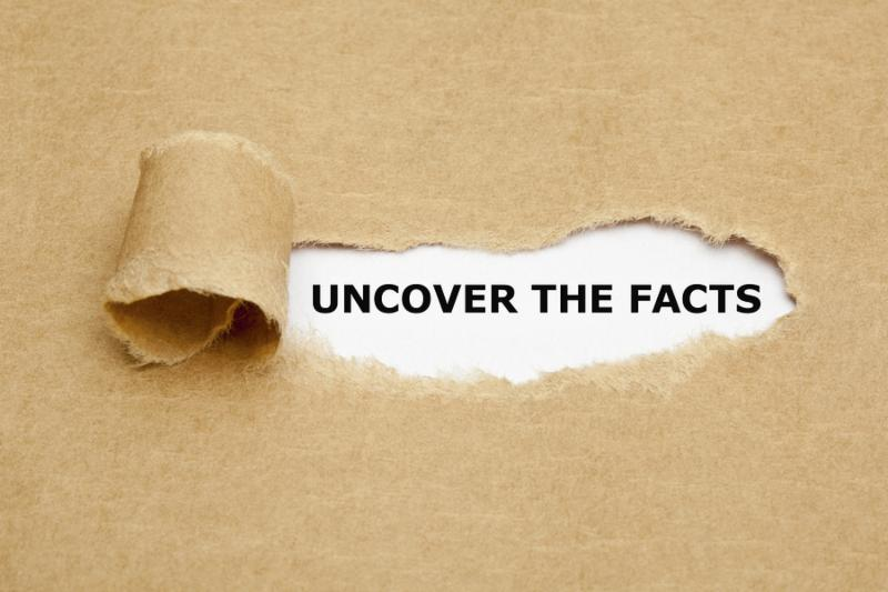 Uncover The Facts appearing behind torn brown paper.     Note  Shallow depth of field