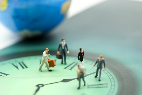 Miniature people   business man walking on the clock background_ time business concept.