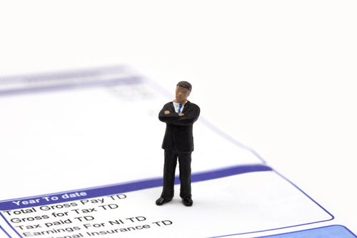 Miniature scale model businessman standing on a wage pay slip showing earnings deductions.  Isolated on a white background