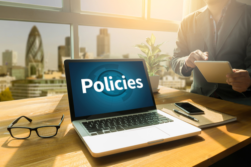 Policies                     Privacy Policy Information Principle Strategy Rules Thoughtful male person looking to the digital tablet screen_ laptop screen_Silhouette and filter sun