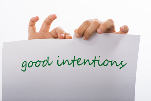 woman tearing sheet with the phrase good intentions